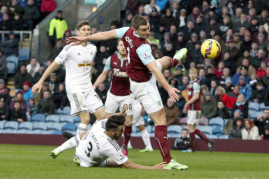 This penalty area challenge by Swansea City's Neil Taylor on Burnley's Sam Vokes was adjudged not to have been a foul<br /> <br /> Photographer Rich Linley/CameraSport<br /> <br /> Football - Barclays Premiership - Burnley v Swansea City - Friday 27th February 2015 - Turf Moor - Burnley<br /> <br /> &copy; CameraSport - 43 Linden Ave. Countesthorpe. Leicester. England. LE8 5PG - Tel: +44 (0) 116 277 4147 - admin@camerasport.com - www.camerasport.com