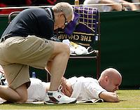 29-6-06,England, London, Wimbledon, second round match,  Melle van Gemerden in pain as he is being treated for a back injury bij fysiotherapist Bill Noris