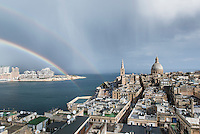 Malta, Valetta, 29 december, 2014<br /> <br /> Late morning view over Valetta, capital of the island Republic of Malta. The approaching rainstorm caused the appearance of a double rainbow over the ancient city. On the left Marsamxett Harbour and the new appartments being built at Tigne Point.<br /> Also visible the tower of St Paul's Anglican Cathedral and the round  Basilica of Our Lady of Mount Carmel.<br /> <br /> <br /> Photo Kees Metselaar