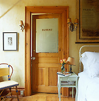 A simple bedroom has been given a French style with a salvaged office door leading to the bathroom and an old map of France above the bed