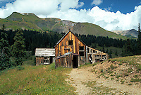 Old wood frame mine shacks provide a rustic contrast to the backdrop of trees and green mountainside. Rocky Mountains, Colorado.