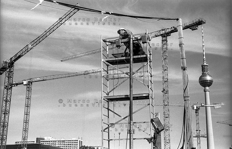 Berlino, quartiere Mitte. Un operaio su un ponteggio tra le gru al cantiere per la ricostruzione del Berliner Schloss (Castello di Berlino). Sullo sfondo a dx: il Fernsehturm (torre della televisione) --- Berlin, Mitte district. A worker on a scaffolding among the cranes at the yard for the reconstruction of the Berliner Stadtschloss (Berlin Palace). On the background: the Fernsehturm (tv tower)