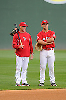 Manager Darren Fenster (3) of the Greenville Drive, left, talks with Red Sox 2014 first-round pick Michael Chavis (11) during batting practice on the team's Media Day first workout of the season on Tuesday, April 7, 2015, at Fluor Field at the West End in Greenville, South Carolina. (Tom Priddy/Four Seam Images)