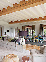 The open-plan sitting room has exposed ceiling beams and a wood floor. The neutral decoration creates a fresh and airy feel whilst the rough wooden dining table and painted chairs give a rustic ambiance.