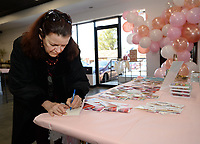 Trish Langdon of Fayetteville fills out a Valentine's Day card Thursday, Feb. 13, 2020, meant for residents at Hillcrest Towers, children in Africa and participants in the Women's Prison Mission during Galentine's Day celebrations at Beautiful Lives Thrift Boutique at 245 E. Township St. in Fayetteville. Galentine's Day is a recently coined holiday combining 'gal' and 'valentine' which celebrates platonic relationships, normally between women. The nonprofit, with locations in Fayetteville, Siloam Springs and Bentonville, financially supports five organizations for global mission work, women and children in crisis and donates clothing to three local charity thrift shops. Visit nwaonline.com/200214Daily/ for today's photo gallery.<br /> (NWA Democrat-Gazette/Andy Shupe)