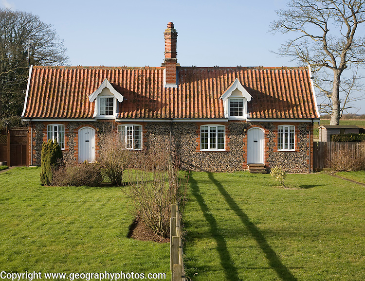 Small symmetrical estate cottages and gardens divided by fence, Suffolk, England