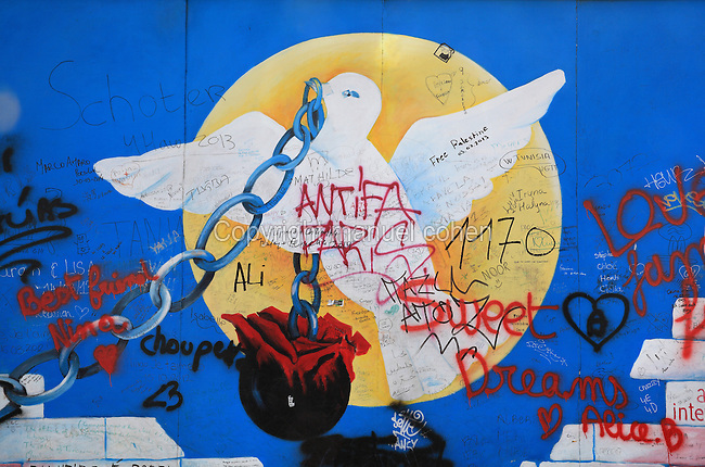 Section of the Berlin Wall depicting an untitled work by Andrej Smolak depicting a dove holding a ball and chain transforming into a rose, damaged by graffiti, part of the East Side Gallery, a 1.3km long section of the Wall on Muhlenstrasse painted in 1990 on its Eastern side by 105 artists from around the world, Berlin, Germany. Picture by Manuel Cohen