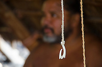 A close-up of a fish hook with a Hawaiian man behind it at Pu'uhonua o Honaunau (City of Refuge), South Kona, Big Island