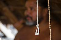 A close-up of a fish hook with a Hawaiian man behind it at Pu'uhonua o Honaunau (City of Refuge), South Kona, Big Island
