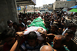 Mourners carry the body of Palestinian Abdul Fattah Abu Azoum 17, who was killed in Israeli tank fire earlier in the day, at the Israel-Gaza border, during his funeral in Rafah in the southern Gaza strip on June 28, 2018. Photo by Ashraf Amra