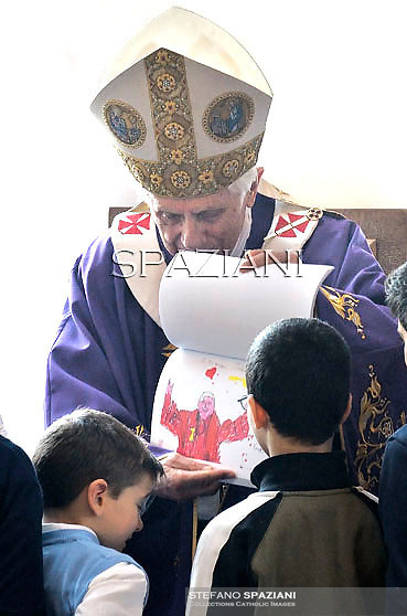 Pope Benedict XVI shows children's drawings he receives as he celebrates mass on March 4, 2012 during his visit at the parish of San Giovanni Battista de La Salle, in the Rome