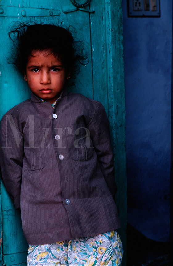 Portrait of an Indian girl with a solemn expression standing in a doorway. Udaipur India.