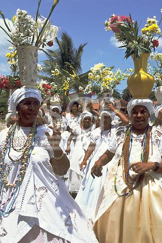 Itaparica Island, Bahia, Brazil. Baiana women carrying flowers on their heads for Iemanja celebration.