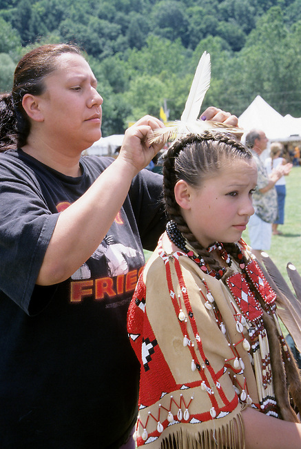 Native American family of a Shawnee mother who ties a feather in her traditionally dressed daughters braided hair during a Pow Wow festival in Mansfield Ohio