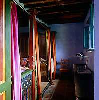 The vivid multicoloured bedding lends a Moroccan flavour to this twin bedroom