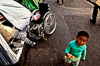 A Handicapped people child goes rounding around the temporary camp in La Paz. A group of handicapped people is tsill protesting in La Paz, Bolivia, to try to be eard by Evo Morales Government, to get a monthly 500 Bs vital bonus (some 60 USD). Government just wait for  them to be tired of protesting since they get to La Paz, one month ago, and don't show signals to look for negotiaitions.