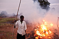 A woman burning grasses in the morning in Madi opei, Northern Uganda. The area is home to thousands displaced by the 20 year conflict with the rebel group The Lord's Resistance Army.