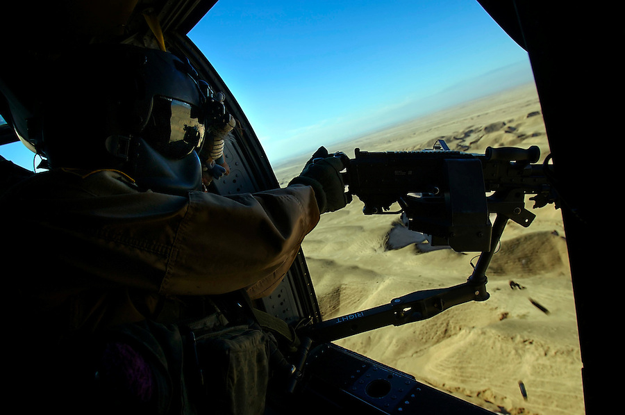 A door gunner aboard an Army Black Hawk helicopter fires on a target in the mountainous desert between Kirkuk and Tikrit  on Sat. Dec. 9, 2006.