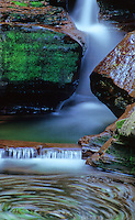 A section of the base of Adams Falls in Rickett's Glen State Park gives a view of swirling water and red rock