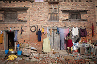 A woman dries clothes hanging them ib front of her house. Shanku, near Kathmandu, Nepal. May 9, 2015