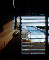 A glimpse through louvered windows of the swimming pool and Tasman Sea beyond