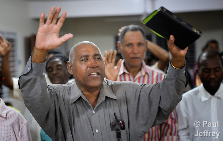 A man prays with raised hands in an evangelical church in La Hoya, a small rural town near Barahona in the southwest of the Dominican Republic. The service brings together Dominicans and Haitian-Dominicans from a nearby batey in an unusual demonstration of unity in a land where discrimination against Dominicans of Haitian ancestry is growing.