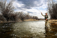 An angler battles a brown trout on the Madison River near Ennis, Montana.