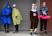 NWA Arkansas Democrat-Gazette/DAVID GOTTSCHALK Runners Ella Quinlan (from right), 14, and her brother Ben, 12, attempt to stay dry with other runners Thursday, November 28, 2019, before the start of the Springdale Turkey Trot at Shiloh Square in Springdale. The event, organized by the Red Dog Club who supports the Springdale High School Bulldogs, featured a  5k, 10k and fun run.