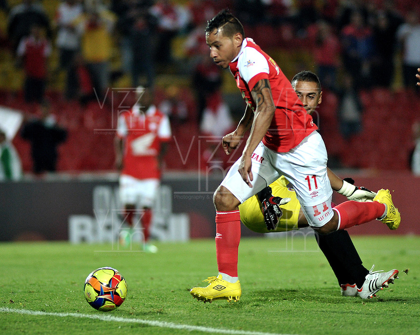 BOGOTA- COLOMBIA -16 -04-2014: Wilder Medina (Izq.) jugador de Independiente Santa Fe disputa el balón con Carlos Perez (Der) jugador de Universidad Autonoma durante partido aplazado entre Independiente Santa Fe y Universidad Autonoma por la fecha 16 entre de la Liga Postobon I 2014, jugado en el estadio Nemesio Camacho El Campin de la ciudad de Bogota. / Wilder Medina (L) player of Independiente Santa Fe vies for the ball with Carlos Perez (R) player of Universidad Autonoma during a postponed match between Independiente Santa Fe and Universidad Autonoma for the date 16th of the Liga Postobon I 2014 at the Nemesio Camacho El Campin Stadium in Bogota city. Photo: VizzorImage  / Luis Ramirez / Staff.