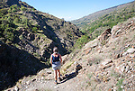 Woman walker and landscape of the River Rio Poqueira gorge valley, High Alpujarras, Sierra Nevada, Granada Province, Spain
