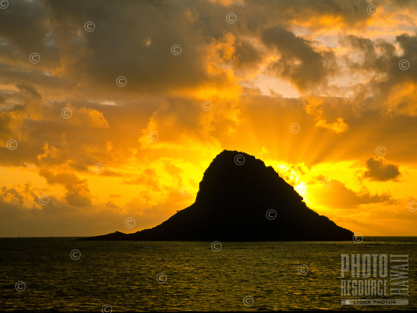 Another colorful sunrise highlights Mokolii Island also known as Chinaman's Hat. Located in Kaneohe Bay on Oahu's windward side.