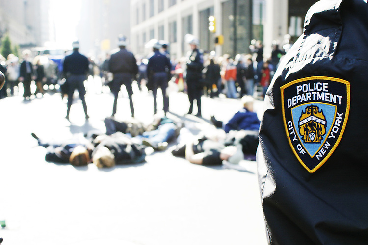 """Hundreds gather at Rockefeller Center in New York City on March 18, 2003 for a """"die-in"""" to protest the invasion of Iraq.  At a chosen time all protesters promptly laid down in the middle of 5th Avenue and were arrested en masse.  The demonstration was organized by the M27 Coalition, beginning a day of multiple direct actions against the war throughout the city.  The M27 Coalition, a loose grouping of activist organizations, chose the locale because if its proximity to various media and corporate offices it professed were profiting, either directly or indirectly, from the war."""