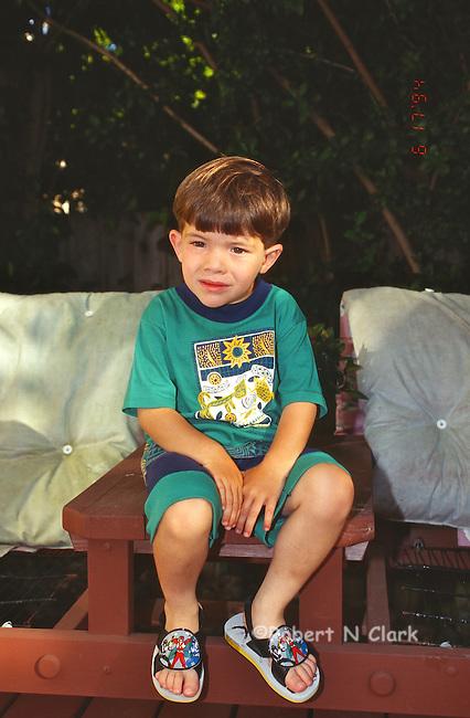 Boy sitting on patio bench