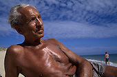 Portugal. Alexander Jakober; suntanned grey haired elderly man reclining on a sunny beach.