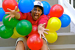 Man sitting on steps with balloons, portrait