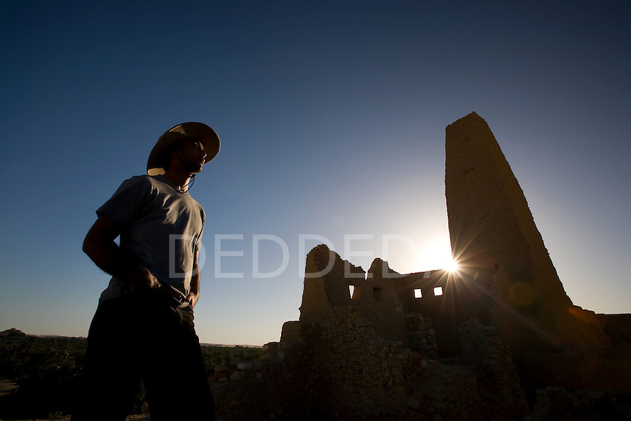 A male tourist at the Temple of the Oracle, dedicated to Amun, built in the 6th century BC and one of the most revered oracles in the ancient Mediterranean, stands in the ruins of Aghurmi village in the Siwa Oasis, Egypt. Alexander the Great consulted the priests of Amun at the Temple of the Oracle in 331 BC.