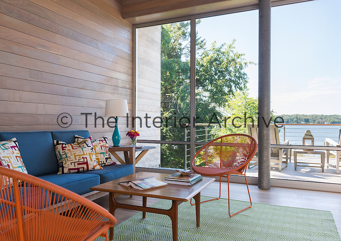 A modern sitting room with a wood panelled wall and a wood floor. A full height picture window allows plenty of light into the room and gives a view of a terrace balcony. The room is furnished with a blue sofa cushions and two orange chairs placed around a coffee table.