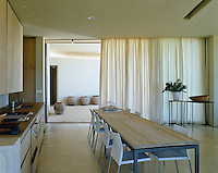 The kitchen and dining area is flanked by  side terraces with sheer curtains across the sliding windows to soften the light