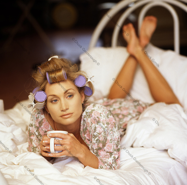 Photo of a Woman in Curlers in the Morning with a cup of Coffee relaxing on a Bed