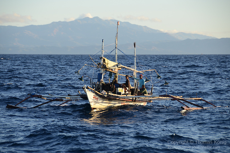 Apo Reef, Sulu Sea -- Fishing outrigger in the Sulu Sea with Mindoro in the background.