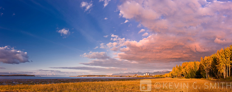 The Anchorage City Skyline and coastal mudflats seen from the Tony Knowles Coastal Trail, Sunset light, fall foliage, fresh snow on the Chugach mountains in the background, Anchorage, Southcentral Alaska, USA.