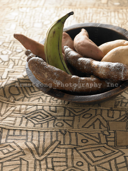 Cassava, plantain, yams, and sweet potatoes, in a wooden bowl on a earth-toned patterned tablecloth.