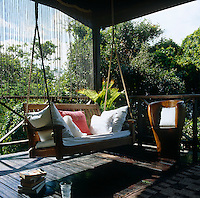 A suspended bench at one end of a covered terrace provides a comfortable alternative for an afternoon siesta