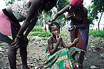 RImage KINSHASA, DEMOCRATIC REPUBLIC OF CONGO - APRIL 30: Esther Yandakwa, age 9, smokes a cigarette while her friends help her with her hair on April 30, 2006 in Matonge district in central Kinshasa, Congo, DRC. Esther is homeless and works a prostitute together with four fourteen-year-old friends. They live outside, next to a polluted river. She's been living three years on the street and has run away from her family. She has from time to time been living in a homeless shelter for but doesn't like the rules there. She usually smokes cigarettes, marijuana, drinks whiskey and sometimes takes Valium. She charges the clients as little as US$ 1. About 15,000 children are estimated to live on the streets of Kinshasa. Congo, DRC is in ruins after forty years of mismanagement by the corrupt dictator and former president Mobuto Sese Seko. He fled the country in 1997 and a civil war started. The country is planning to hold general elections by July 2006, the first democratic elections in forty years. (Photo by Per-Anders Pettersson)