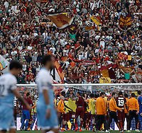Calcio, Serie A: Lazio vs Roma. Roma, stadio Olimpico, 25 maggio 2015.<br /> Roma players, in background, celebrate as Lazio players leave the pitch at the end of the Italian Serie A football match between Lazio and Roma at Rome's Olympic stadium, 25 May 2015. Roma won 2-1.<br /> UPDATE IMAGES PRESS/Isabella Bonotto