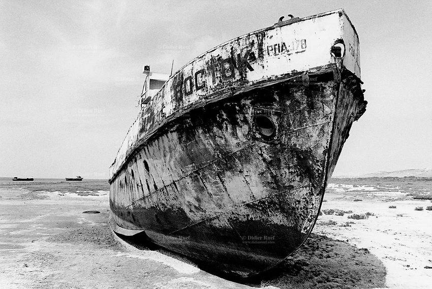 Kazakhstan. Agyspe. Aral sea. An ambitious undertaking through dams construction aims to reverse one of the world's man-made environmental disaster and bring back the sea. The water is returning to the kazak Aral sea (small Aral) and is now 100 meters distant from the dried up (dry bed) Sea where abandoned russian fishing boats litter the dry landscape where the Aral sea once called home until it started to dry up due to overuse of water resources at the time of  former Soviet Union. The causes were human and environmental effects of industrial pollution with consequences for the Aral sea to dry up, then shrink and become now two shallow lakes far from the old shore. © 2008 Didier Ruef ... ..