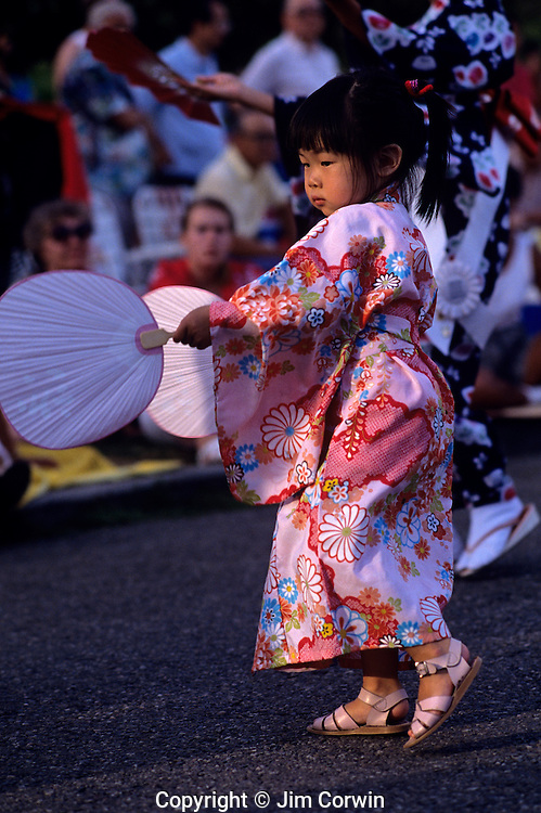 Young girl in Bon Odori celebration and parade with dancers with fan celebrating Seattle Washington State USA