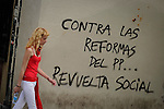 """A woman walks in front of a banner that says """"against the reforms  popular Party (PP) social revolt"""" during San Fermin Festival bull run, on July 12, 2012, in Pamplona, northern Spain. The festival is a symbol of Spanish culture that attracts thousands of tourists to watch the bull runs despite heavy condemnation from animal rights groups. (c) Pedro ARMESTRE"""