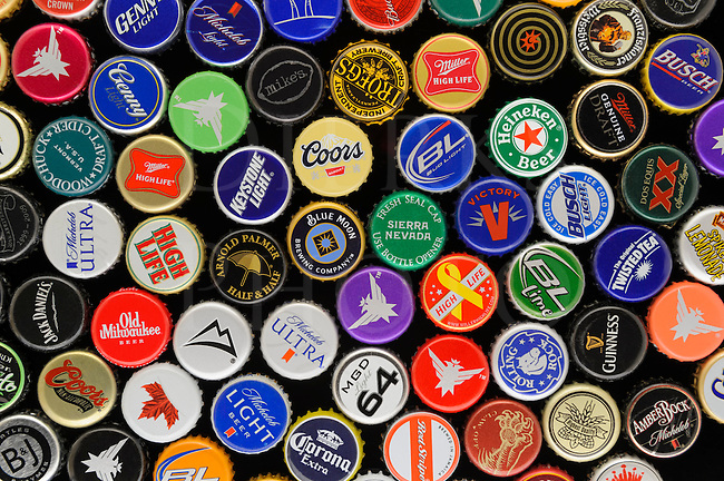 Beer bottle caps in a colorful variety assortment on a black background, great for decorating a man cave!