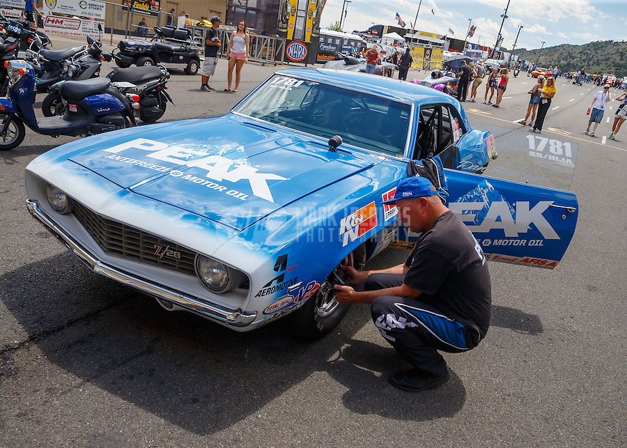 Jul 24, 2016; Morrison, CO, USA; NHRA super stock eliminator driver Dan Fletcher checks the tire pressure on his car during the Mile High Nationals at Bandimere Speedway. Mandatory Credit: Mark J. Rebilas-USA TODAY Sports